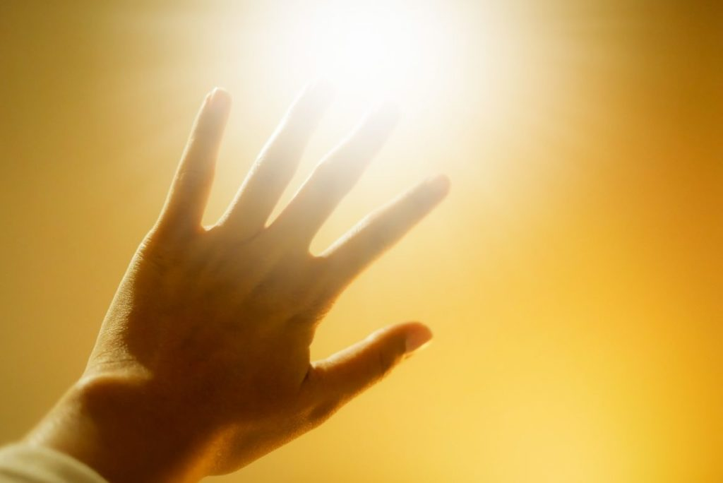 Hand outstretched to block the bright sun.Photophobia is a common symptom of Ocular Albinism. eSight glasses for the visually impaired can help with light sensitivites.