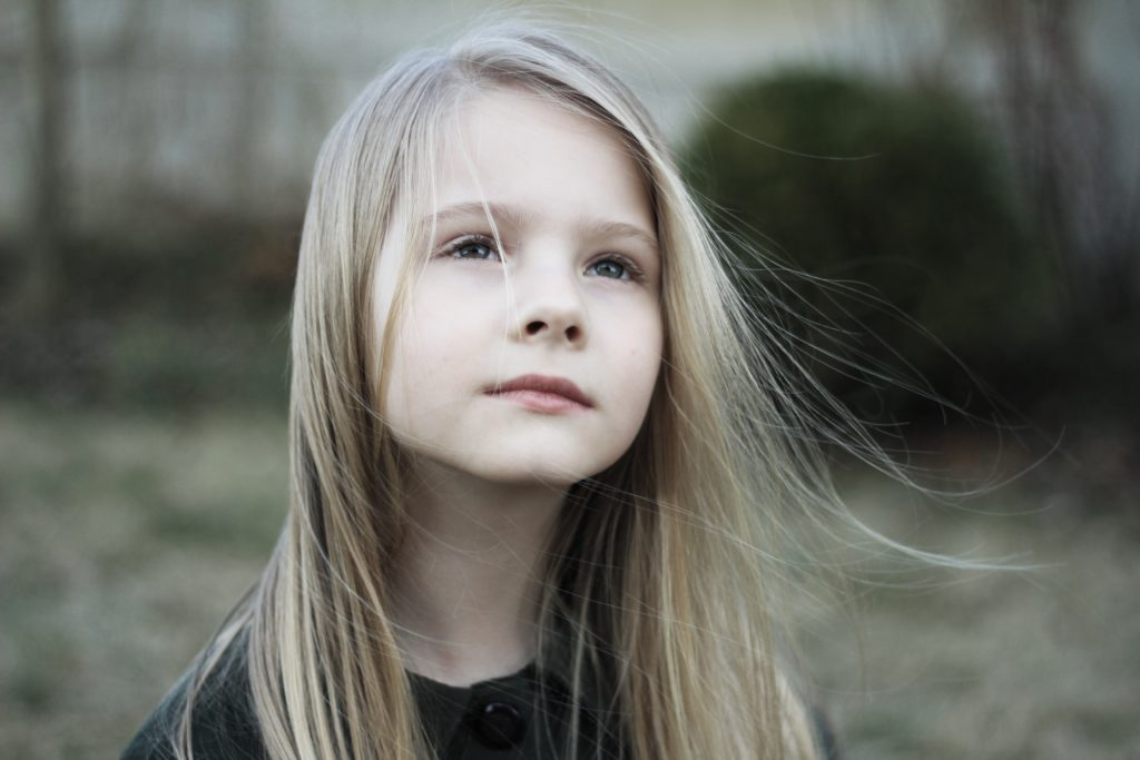Young girl looking wistfully into the distance. Stargardt's disease is often diagnosed in childhood.