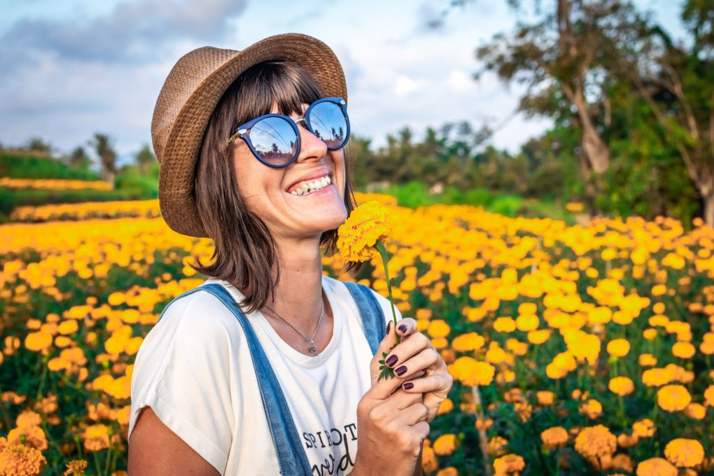 Woman with Stargardt's disease is wearing wide-brimmed hat, glasses and sunglasses in a flower field.