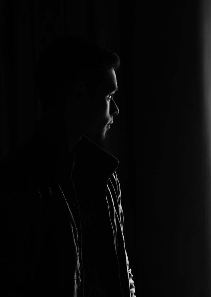 A dark photo with an outline of a man. A representation of night vision that someone with Retinitis Pigmentosa would see. eSight glasses for the visually impaired can enhance contrast and provide a more clear image.