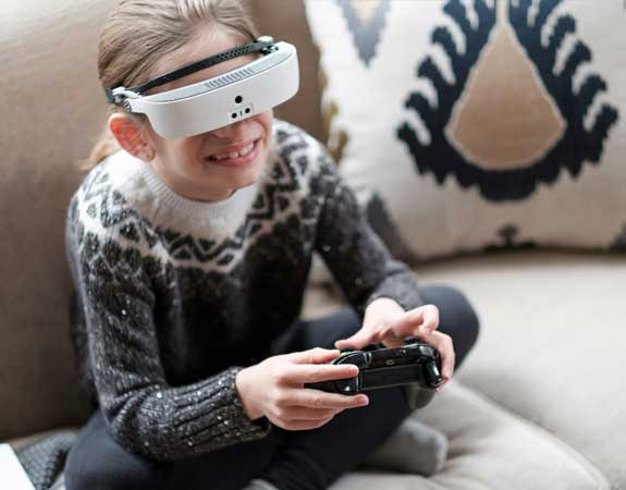 Young girl plays video games using her eSight