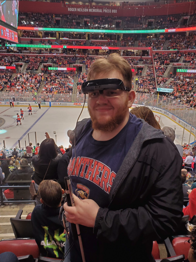 21-year-old man living with ONH watches a live hockey game using his low vision aid, eSight 3