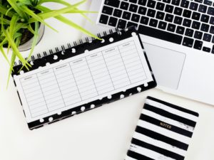 Daily planner lying on a laptop along with a notebook. Part of eSight Eyewear's accessible entertainment