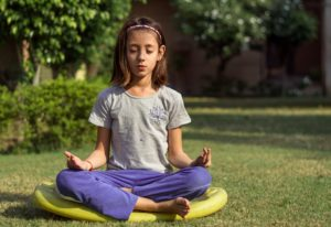 Young girl meditating outside. Part of eSight Eyewear's tips for parents of low vision children