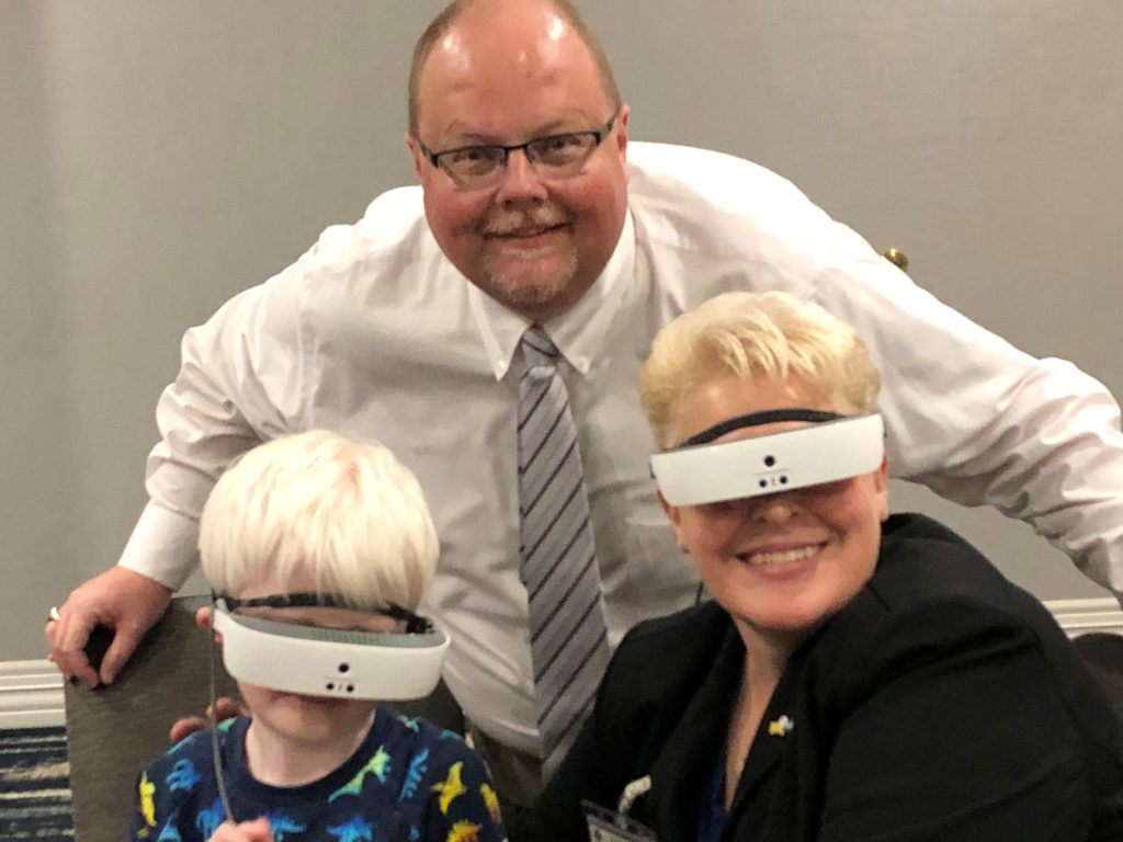 Dr. Mary pictured with 5-year-old boy using eSight Eyewear. The Collins boy has lived with Ocular Albinism his entire life