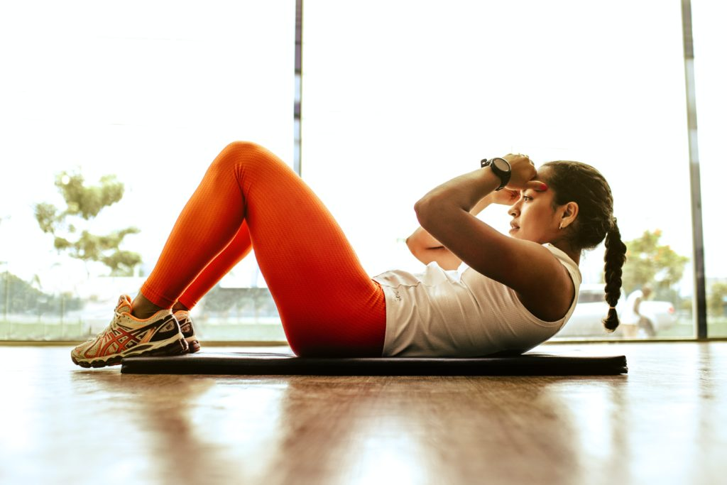Woman doing sit-ups, exercise helps prevent macular degeneration
