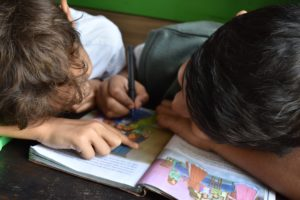 Two young students looking at a picture book.