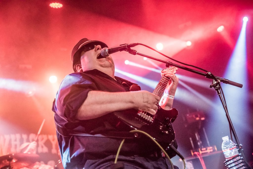 Blind musician Joey Stuckey passionately singing while playing guitar on stage