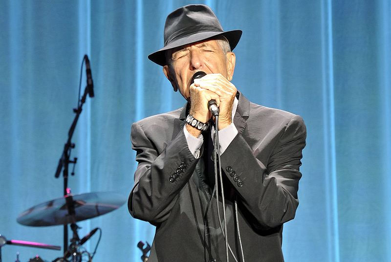 Leonard Cohen performing on-stage.